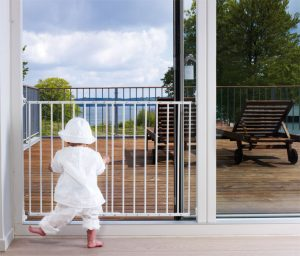 Child looking through BabyDan multiDan gate at open sliding door