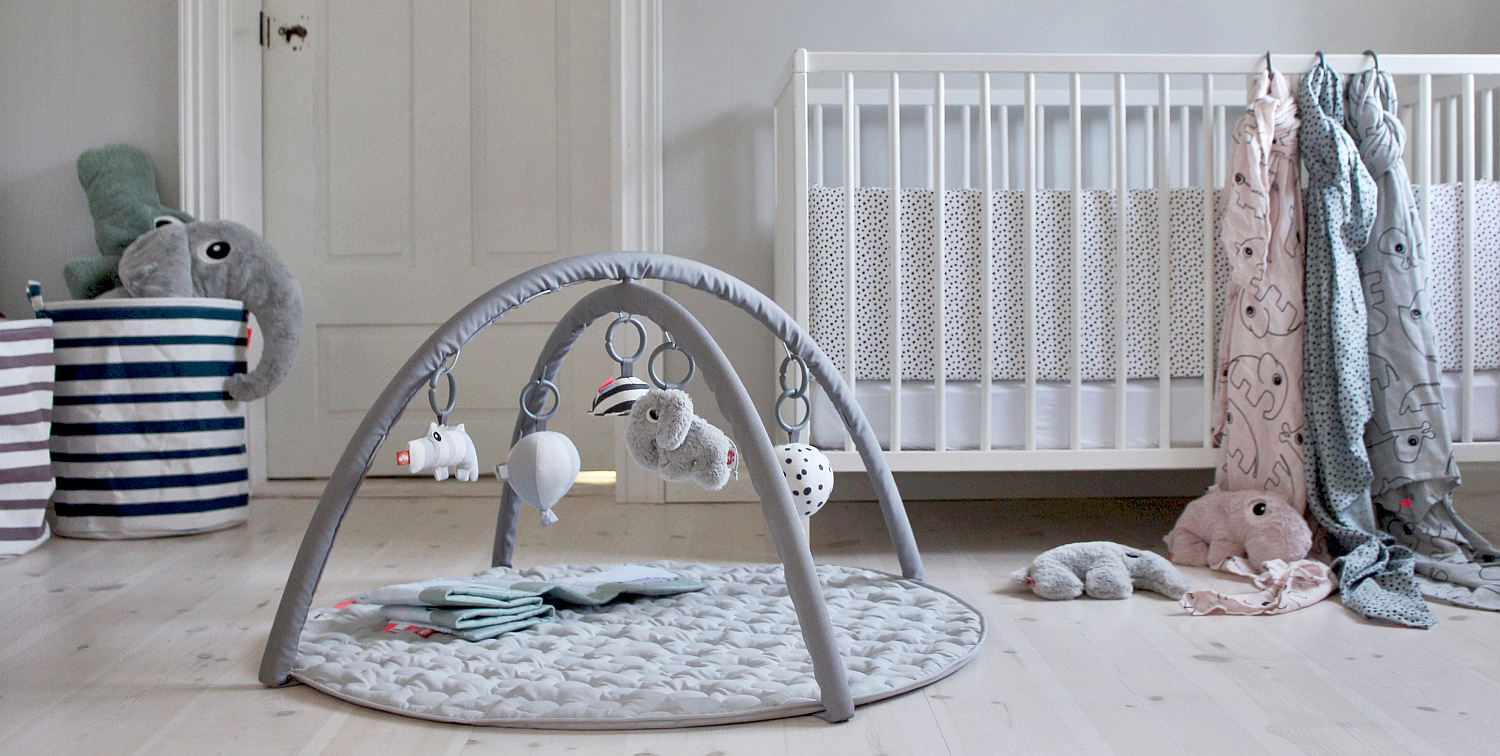 Done by deer activity playmat in grey in front of cot in nursery