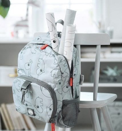 Done by Deer grey backpack with rolls of posters hanging on chair