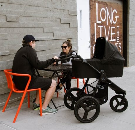 Parents with black Bumbleride Speed stroller fitted with bassinet at city cafe