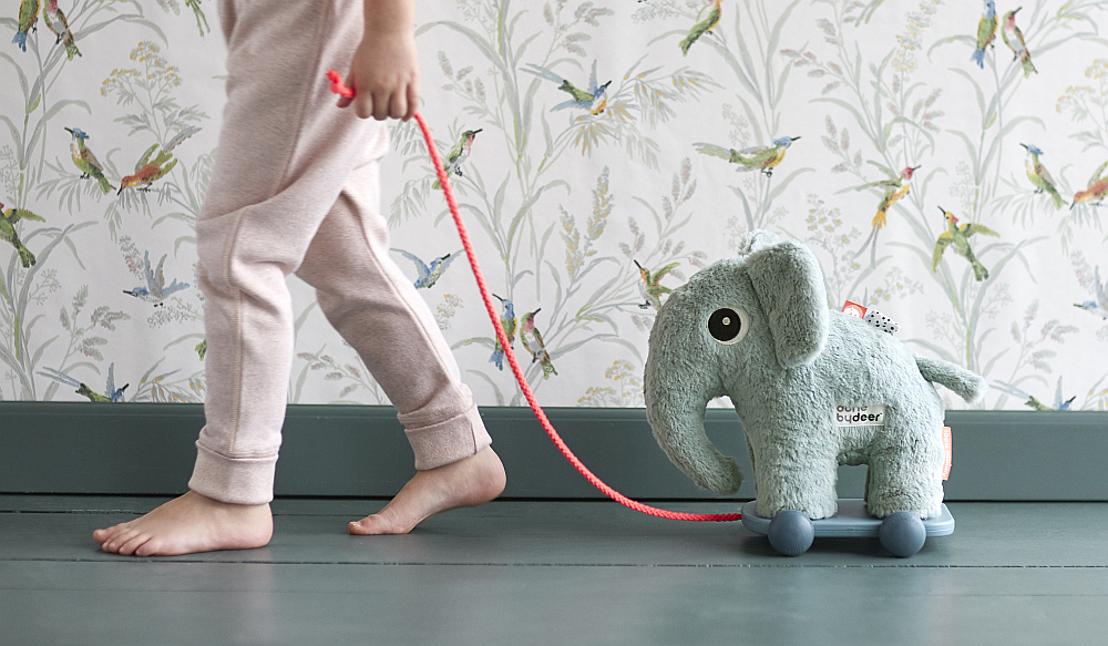 child pulling elephant toy on trolley