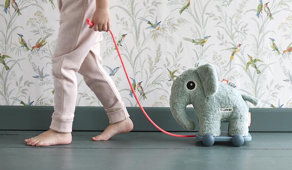 child pulling elephant toy on trolley
