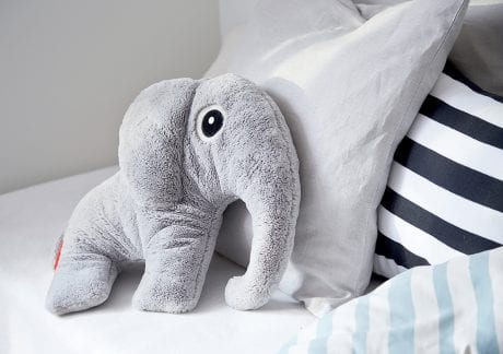 Large grey plush elephant from Done by Deer resting on bed