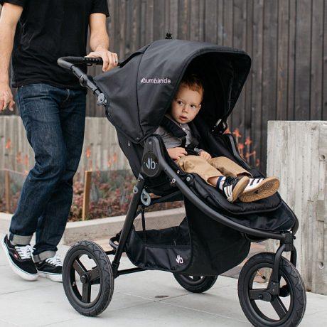 Dad pushing boy in Bumbleride Indie pram in black with black frame