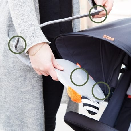 Mother with pram shows how to attach the done by deer clip on mirror