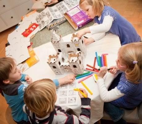 kids craft group session at table with cardboard model and textas