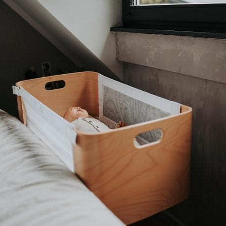 Baby sleeping in Bednest bedside bassinet in bedroom with both sides up