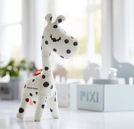 Cute white baby giraffe rattle with black dots standing on table