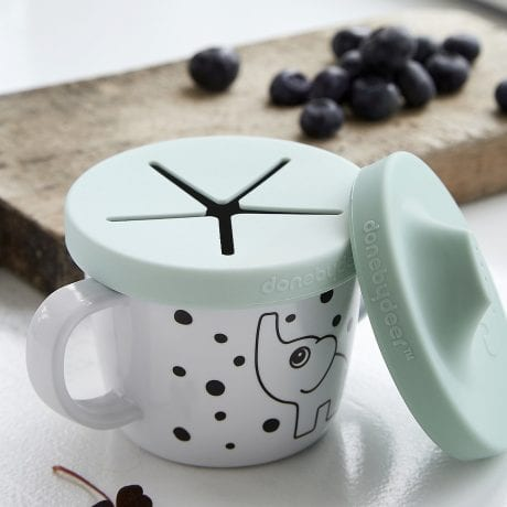 Done by Deer spout and snack cup with elephant print and blue silicone lid on table