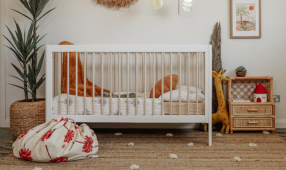 Troll Lukas cot in white in rustic bedroom with red and natural accents