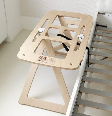 Bednest bassinet stand secured to bed frame with straps