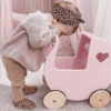 Little girl loking into Moover Classic Pram in pink